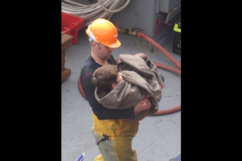 Crew member Juan Owens helps the boy ashore