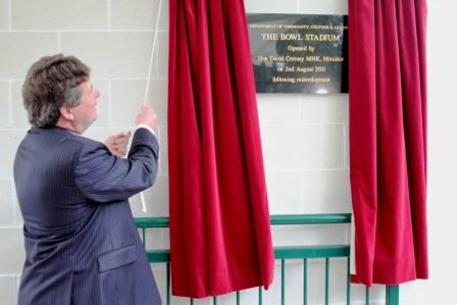 Minister David Cretney unveils the plaque at the official opening of the Bowl Stadium