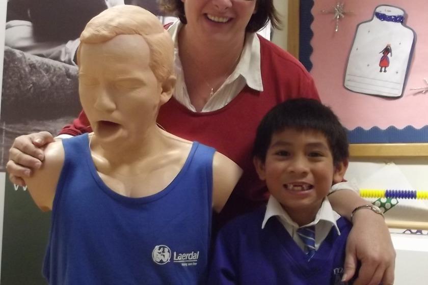 Lucky Richmond Gabriel with teacher Jo Callow and St John Ambulance training aid 'Choking Charlie'