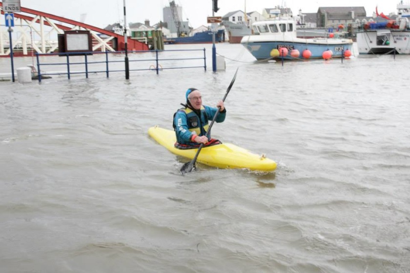 A man kayaks through the streets in Ramsey - by Bill Dale