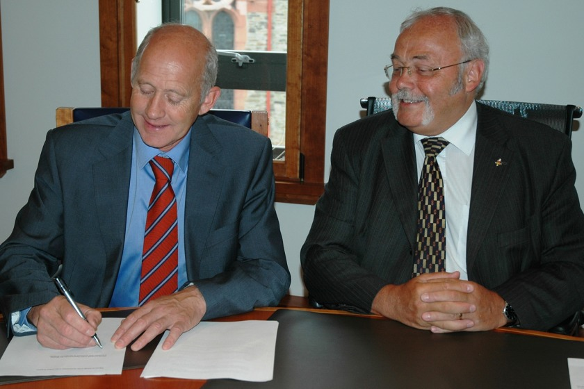 Chief Minister Tony Brown watches as Health Minister David Anderson signs the agreement